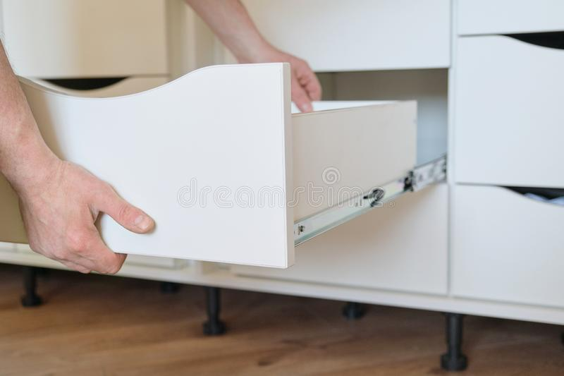 Installation of furniture. Closeup of workers hand and furniture details stock image