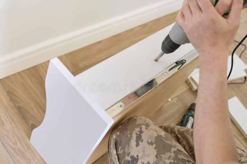 Installation of furniture. Closeup of workers hand with professional tools and furniture details royalty free stock photo