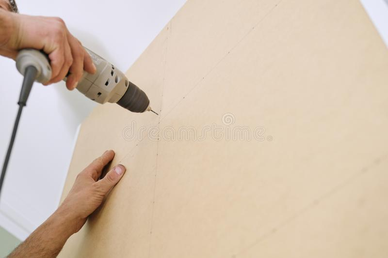 Installation of furniture. Closeup of workers hand with professional tools and furniture details stock image