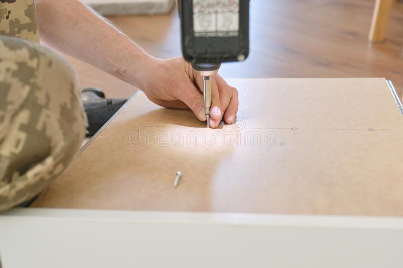 Installation of furniture. Closeup of workers hand with professional tools and furniture details stock photo