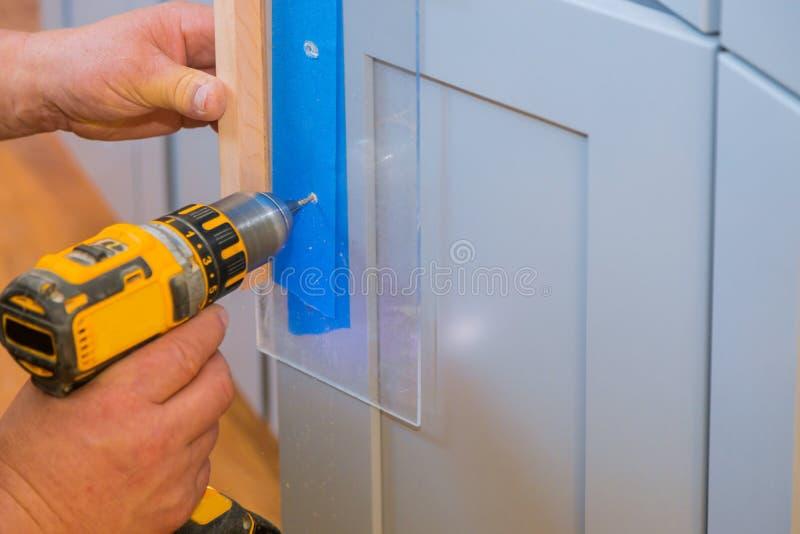Master drills the cabinet door in the cabinet door. Installation of furniture hinges on the cabinet door master drills the door in the cabinet door, screwdriver stock photos