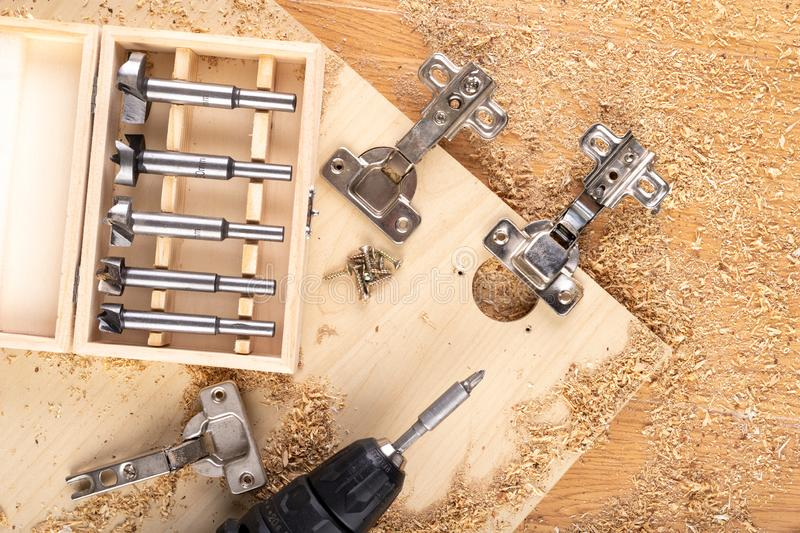 Installation of furniture hinges in chipboard. Small carpentry work in the workshop stock images