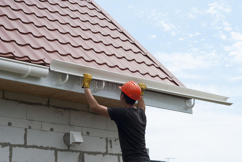 Installation of gutter system. Worker installs the gutter system on the roof royalty free stock photography
