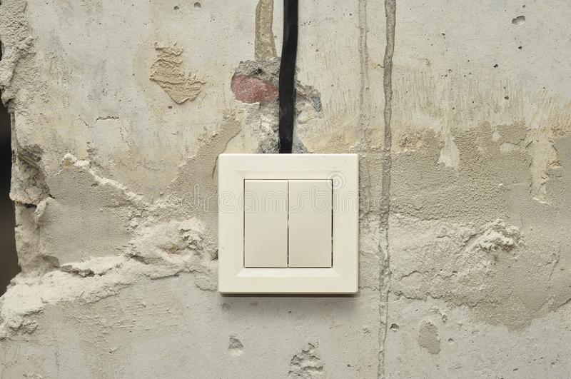Installation of light switches when repairing fresh concrete empty walls royalty free stock photos