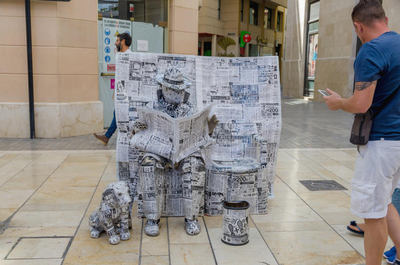 Installation of man reading newspaper with dog stock image
