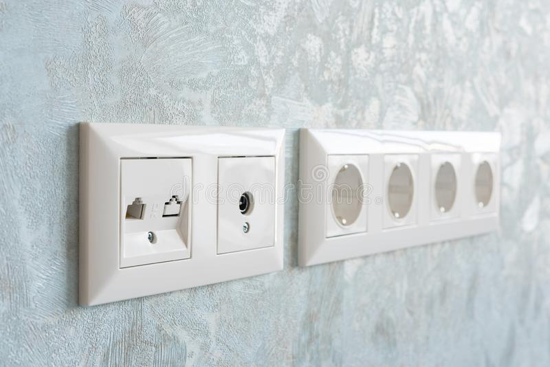 Installation of modern power, communication LAN RJ45 and television sockets on a wall close-up. royalty free stock photo