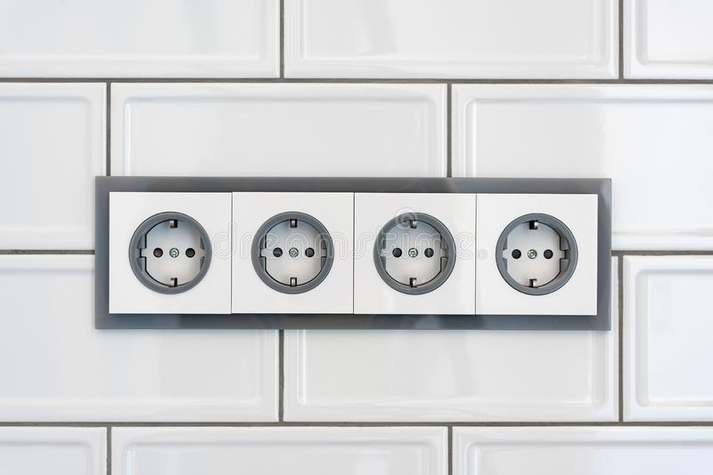 Installation modern sockets on a tile wall close-up. Grey and white electrical outlet. stock photo