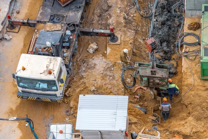 Installation of piles at a building site using an outboard power plant for drilling soil.  stock photo