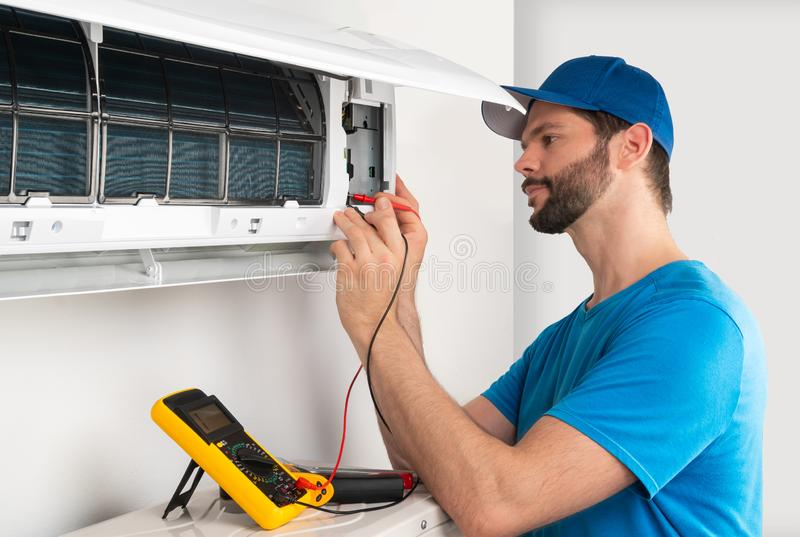 Installation service fix repair maintenance of an air conditioner indoor unit, by cryogenist technican worker with multimeter stock photo