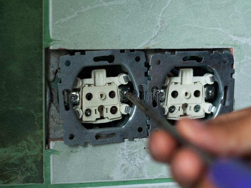 Installation of sockets in niches carved by the crown, the electrician fixes the wall sockets in the bathroom with  a screwdriver. Close-up royalty free stock images