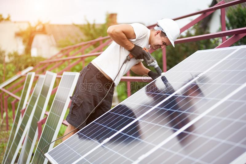 Installation of stand-alone exterior photo voltaic panels system. Renewable green energy generation. Back view of young technician in helmet connecting solar royalty free stock photo