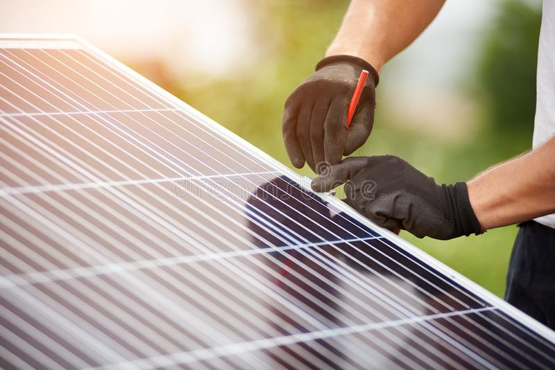 Installation of stand-alone exterior photo voltaic panels system. Renewable green energy generation. Close-up technicians hands in protective gloves making mark royalty free stock photo
