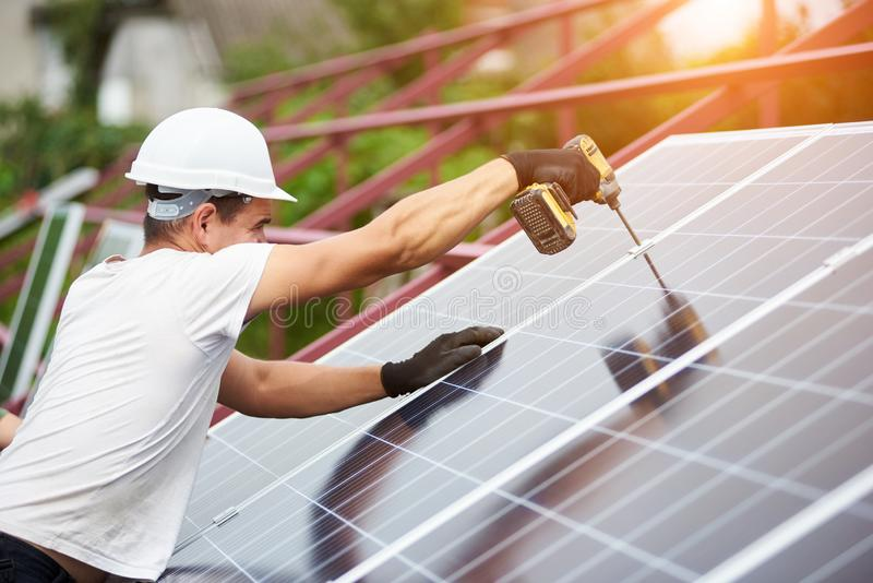 Installation of stand-alone exterior photo voltaic panels system. Renewable green energy generation. Professional technician working with screwdriver connecting stock photography