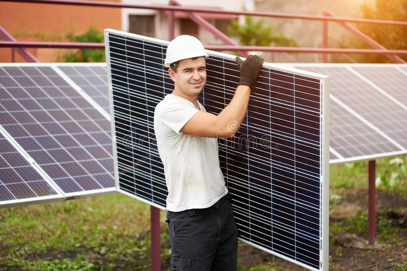 Installation of stand-alone exterior photo voltaic panels system. Renewable green energy generation. Smiling young worker in protective helmet carrying big royalty free stock image