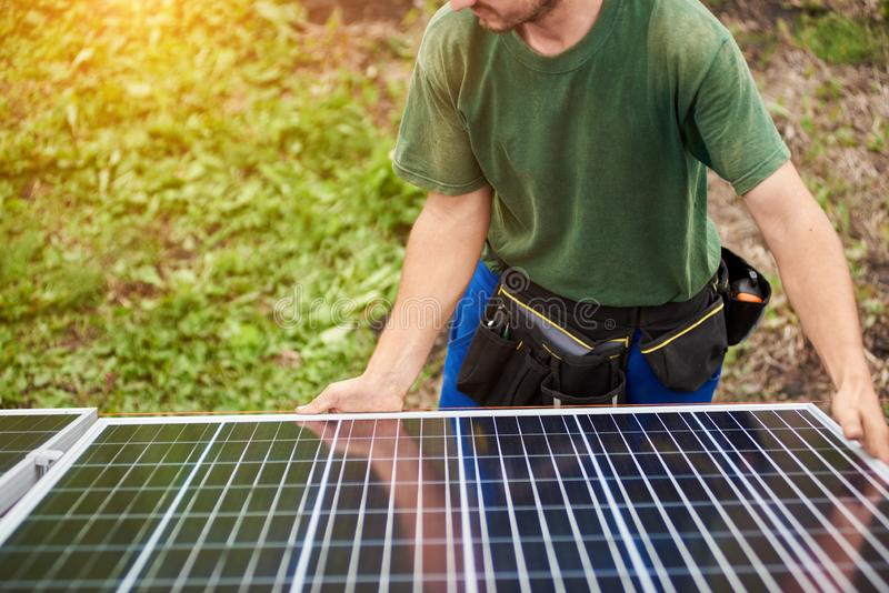 Installation of stand-alone exterior photo voltaic panels system. Renewable green energy generation. Team of technicians adjusting big shiny solar panel to stock photography