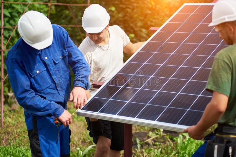 Installation of stand-alone exterior photo voltaic panels system. Renewable green energy generation. Team of technicians holding and taking measurement of big stock images