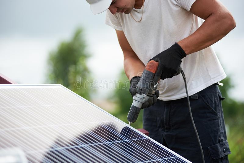 Installation of stand-alone exterior photo voltaic panels system. Renewable green energy generation. Technician worker assembling shiny solar photo voltaic stock photos