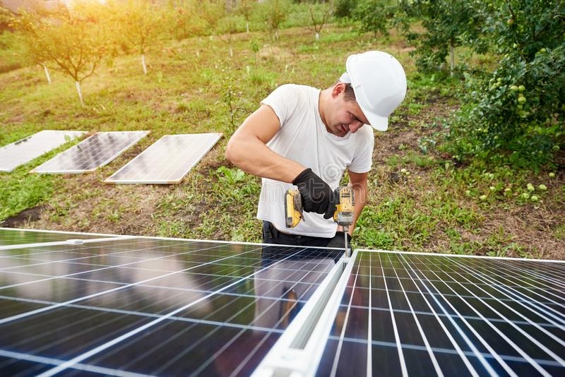 Installation of stand-alone exterior photo voltaic panels system. Renewable green energy generation. Young technician working with screwdriver connecting solar stock photo