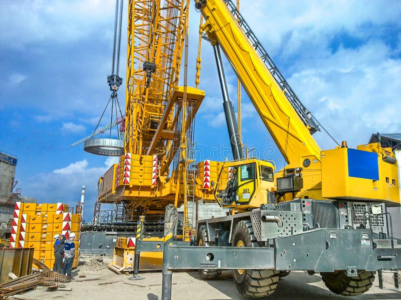 Installation of technological equipment on the construction site. Using a crawler and a wheeled crane royalty free stock photos