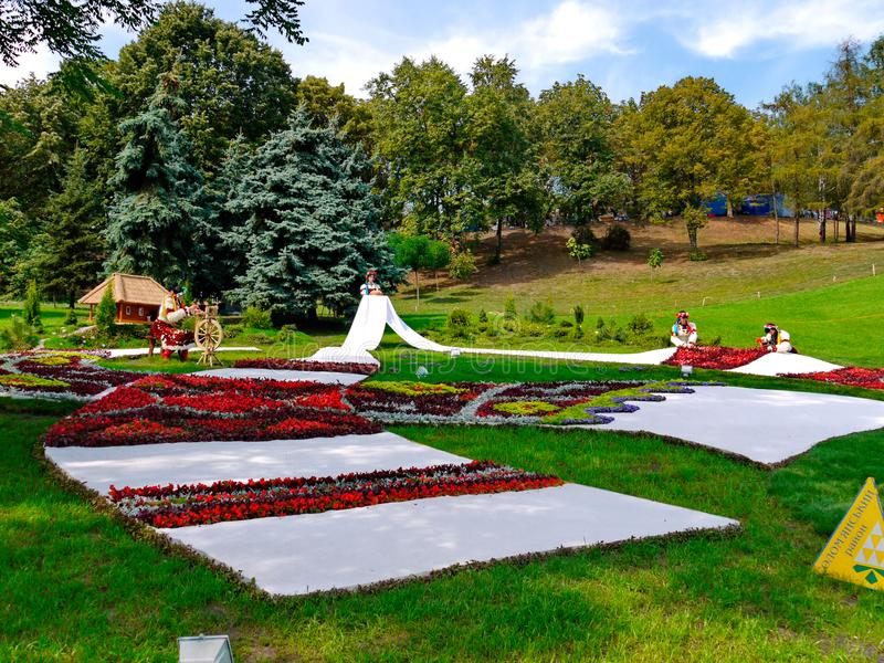 Installation in the Ukrainian style with the girls who embroider a towel passing into the flower bed. For your design royalty free stock photo