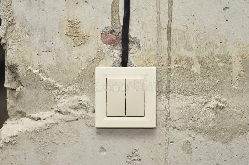 Installation von Lichtschaltern, wenn leere Wände des Frischbetons repariert werden lizenzfreie stockfotos