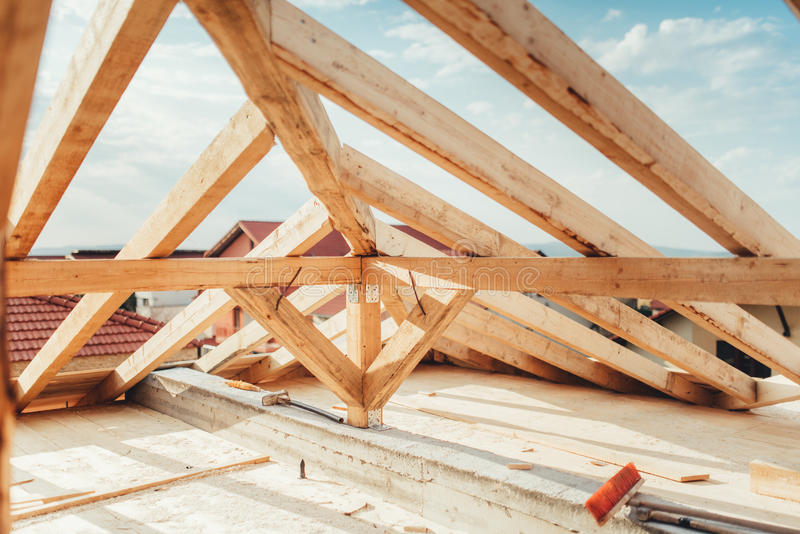 Installation of wooden beams at house construction site. Building details with wood, timber and iron holders royalty free stock image