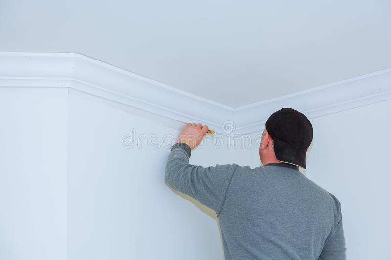 Installation of ceiling moldings. Worker fixes the wood molding to the ceiling. Installation of worker fixes the wood crown molding to the ceiling stock image