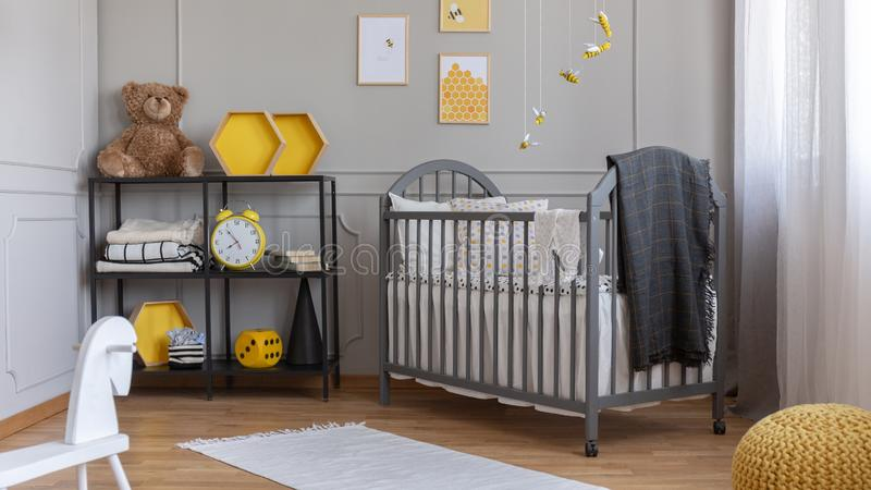Installation with yellow and black bees above grey wooden crib with blanket and pillow. Installation with yellow and black bees above grey wooden crib with and stock photos