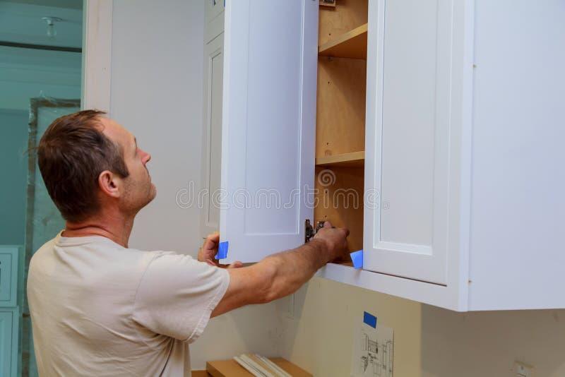Installationskök Arbetaren installerar dörrar till köksskåpet royaltyfri bild