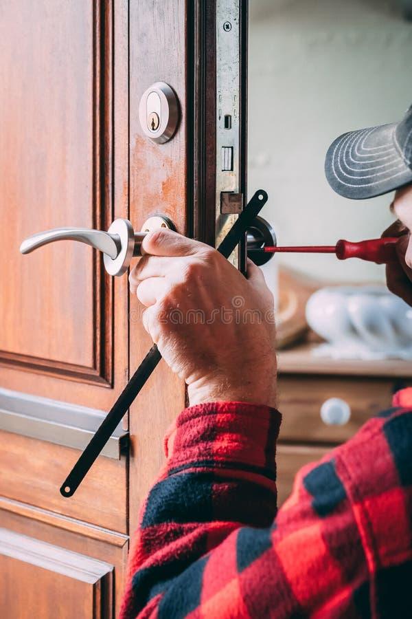 Installazione del carpentiere di nuova maniglia della porta fotografia stock libera da diritti