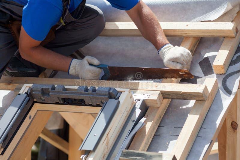 Installazione del lucernario L'uso del lavoratore del costruttore del Roofer ha visto per tagliare un fascio di legno fotografia stock libera da diritti