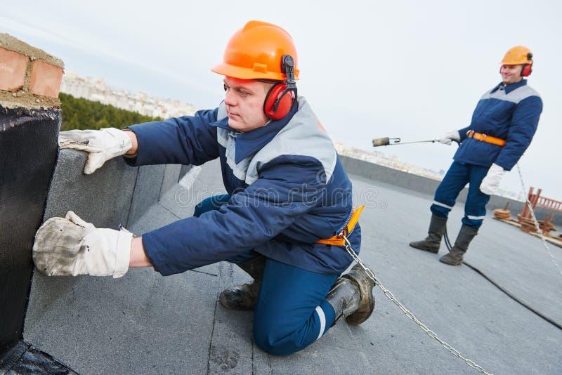 Installazione del tetto piano Feltro di riscaldamento e di fusione del tetto del bitume fotografia stock libera da diritti