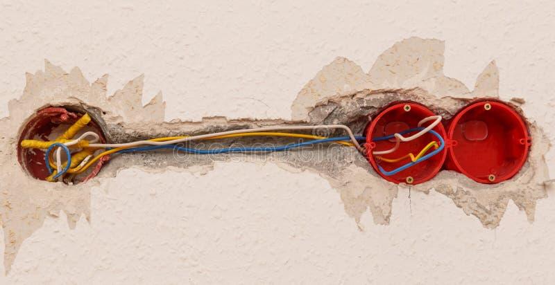 Installazione dell'incavo di elettricità sulla parete bianca fotografia stock
