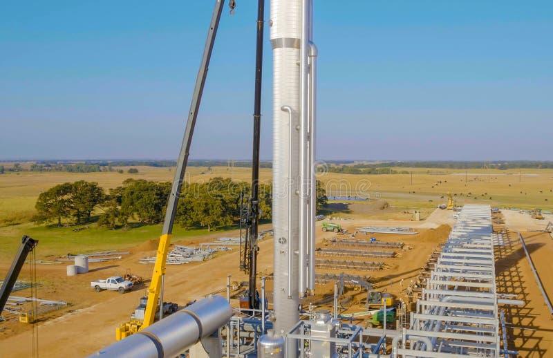 Installazione della colonna di distillazione con una gru dell'ascensore Costruzione di una raffineria di petrolio fotografia stock