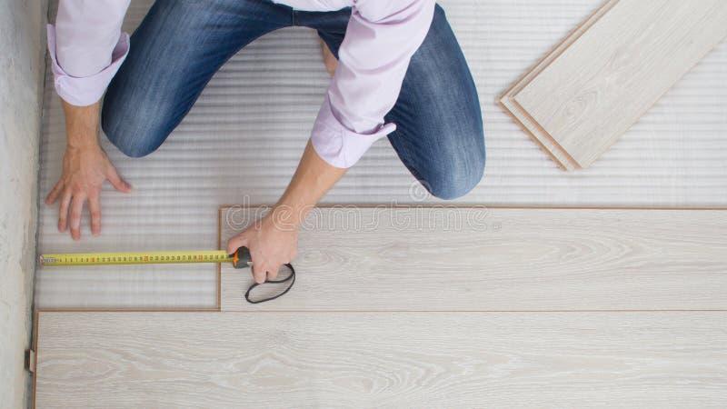 Installazione della pavimentazione laminata di legno fotografia stock