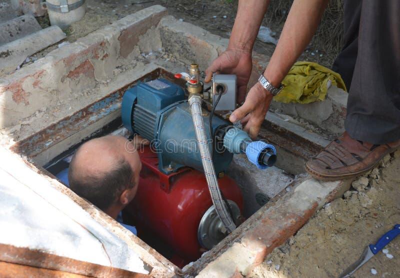 Installazione della pompa idraulica del pozzo trivellato Appaltatori che intalling e stazione di pompa idraulica di riparazione fotografia stock libera da diritti