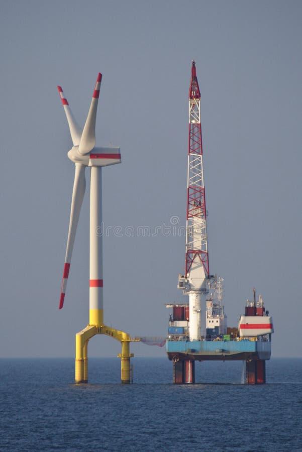 Installazione della turbina di vento di terra nel mare fotografie stock
