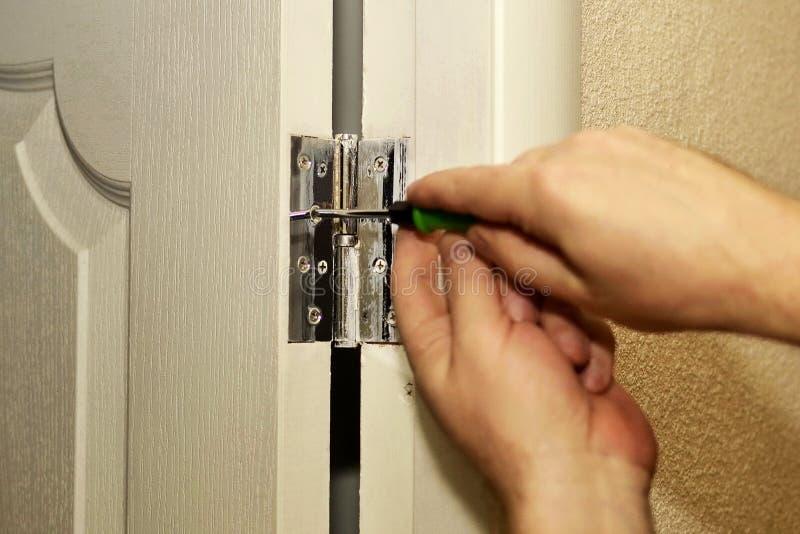 Installazione delle cerniere di porta, riparazioni nell'appartamento fotografia stock libera da diritti