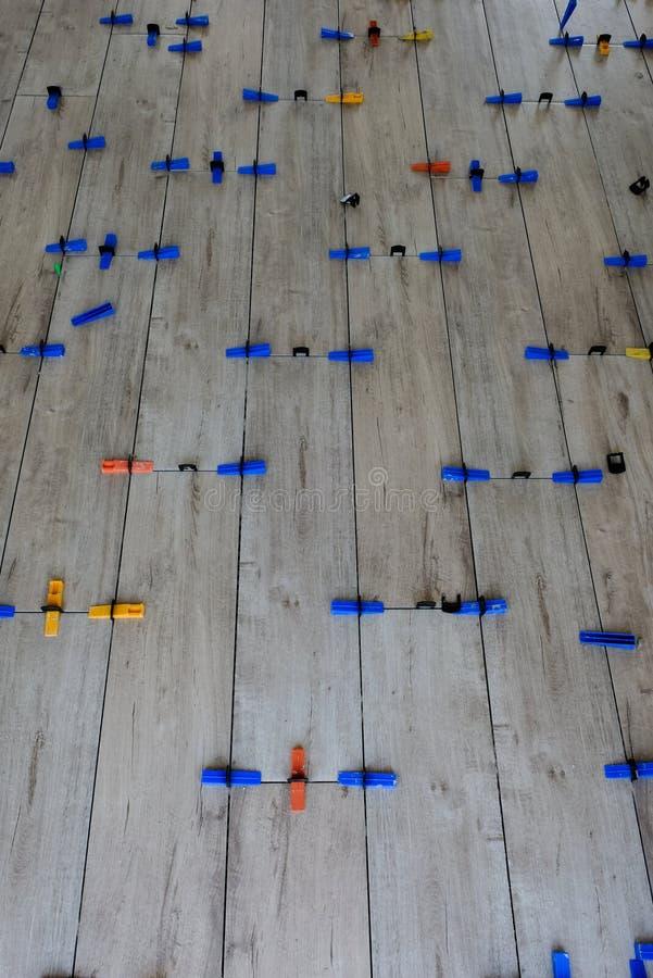 Installazione delle mattonelle stile legno della porcellana su un pavimento immagini stock libere da diritti