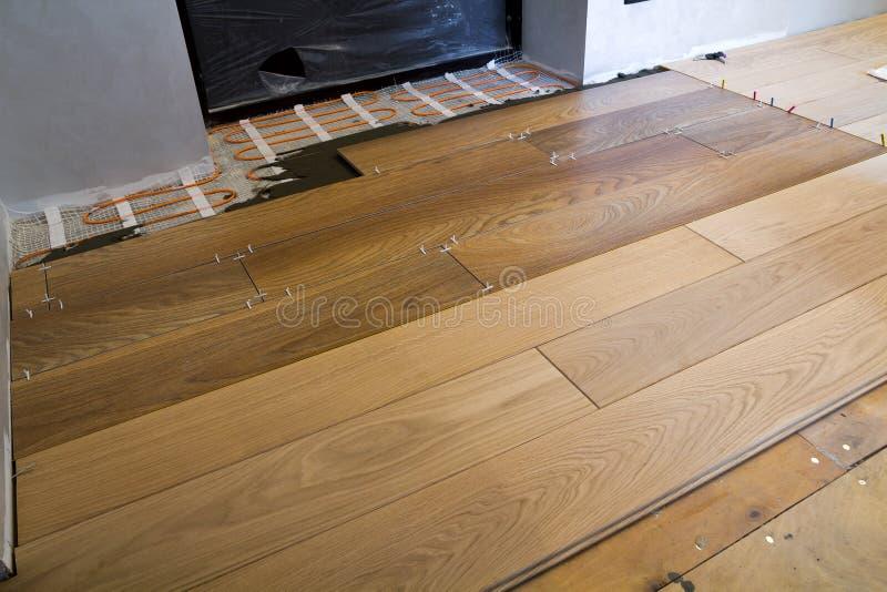 Installazione delle piastrelle di ceramica e degli elementi riscaldanti in pavimentazione in piastrelle calda Concetto di miglior fotografia stock