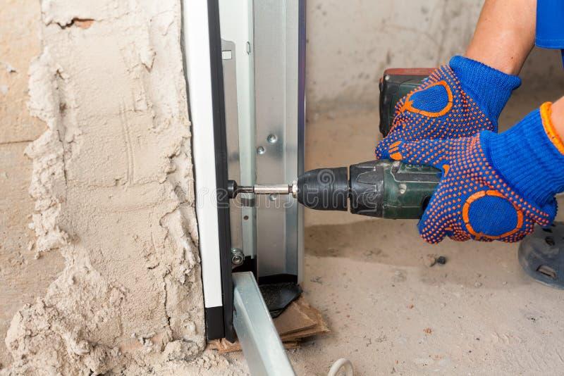 Installazione delle porte del garage Cacciavite automatico di uso del lavoratore per riparare un bullone fotografie stock libere da diritti