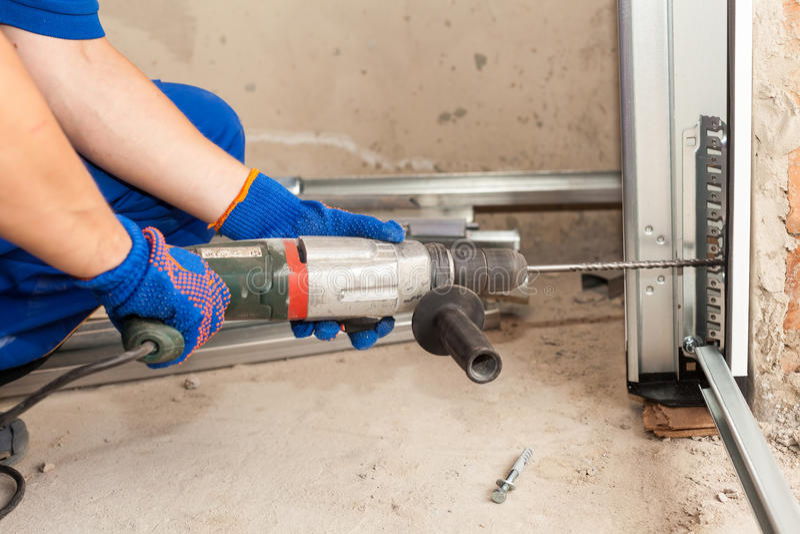 Installazione delle porte del garage Il lavoratore perfora un pozzo per il bullone fotografia stock libera da diritti
