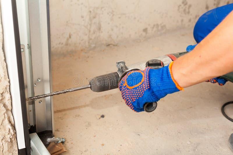 Installazione delle porte del garage Il lavoratore perfora un pozzo per il bullone immagine stock libera da diritti