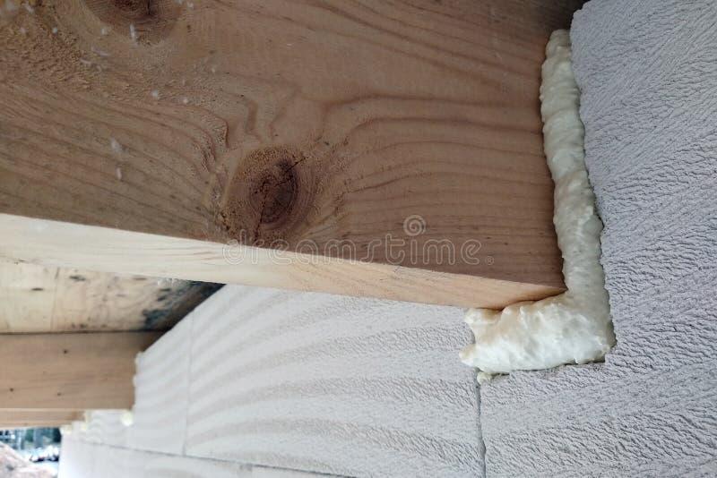 Installazione di fasci di legno di telaio di tetto con schiuma a spruzzo su una parete interna in costruzione fotografia stock