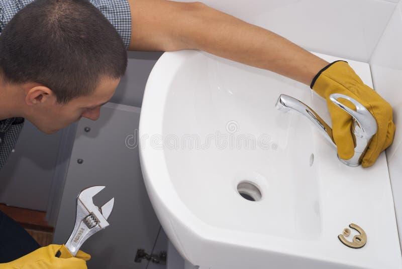 Installazione di un rubinetto per un lavandino immagine stock libera da diritti
