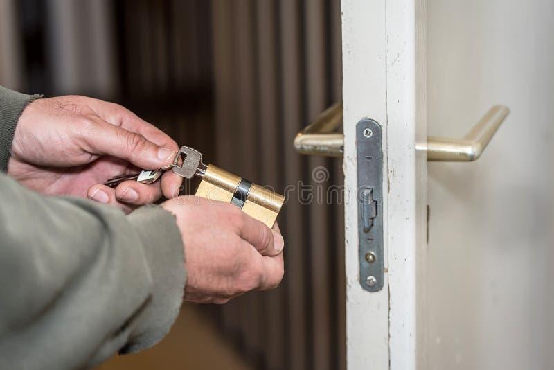 Installazione o riparazione di legno della serratura di porta del lavoratore maschio del tuttofare immagini stock libere da diritti