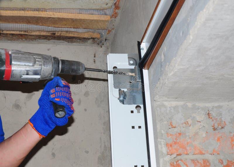 Installazione & sostituzione della porta del garage Installi la porta del garage & il luogo di perforazione per le primavere dell fotografia stock libera da diritti