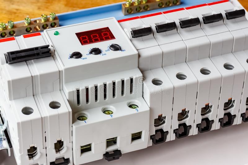 Installed automatic circuit breakers with voltage limiter in the white plastic mounting box closeup stock photo