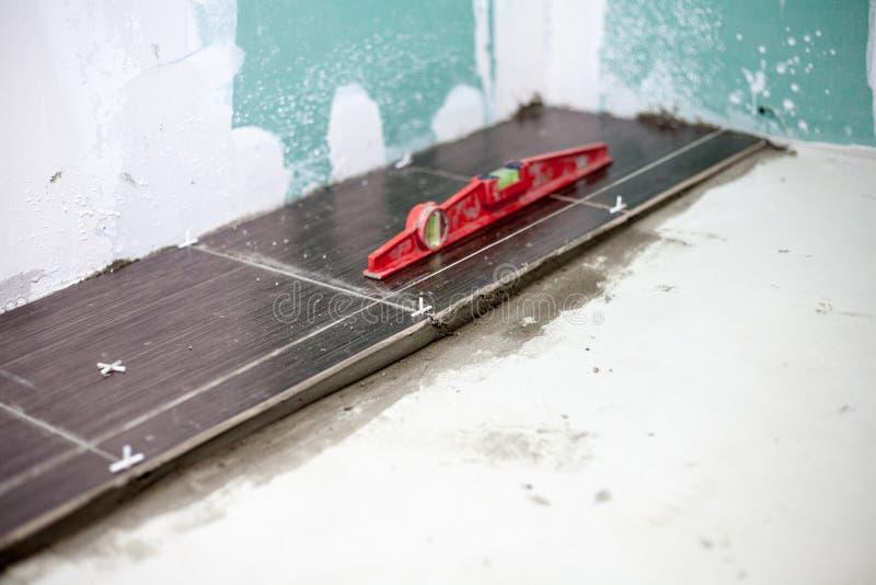 Installera keramiska golvtegelplattor - mäta och klippa styckena, closeup arkivbild