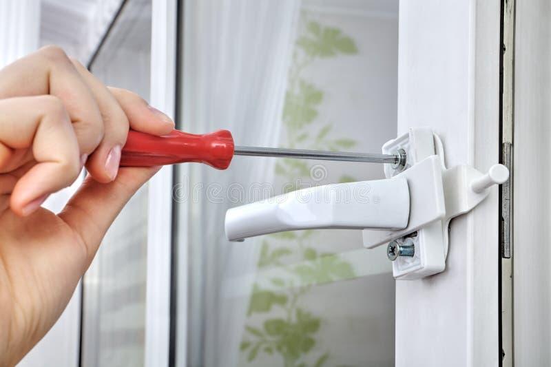 Installera limiteren för plast- fönster, genom att använda en skruvmejsel, closen- royaltyfria foton